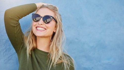 woman with blonde hair wearing sunglasses smiling in front of a blue wall