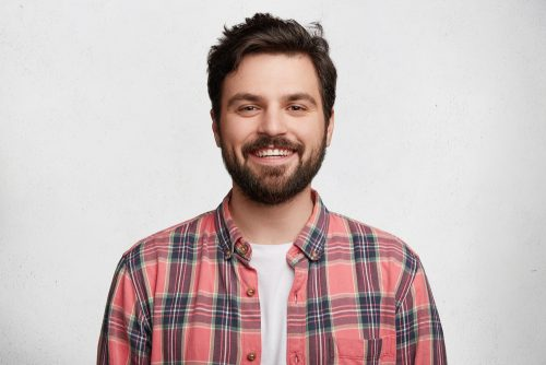 man in a plaid shirt smiling in front of a white wall
